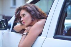 Kvinna i den vita bilen som ser borrad royaltyfria bilder
