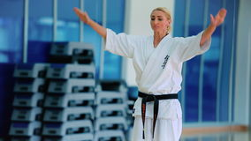 Kvinna i den vita kimonot som öva några trick i idrottshallen lager videofilmer