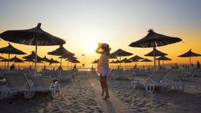 Kvinna i den vita klänningdansen på den tomma stranden på solnedgången Royaltyfria Bilder