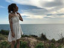 Kvinna i den vita klänningen på berget som ser till havet med solnedgång och blå himmel royaltyfria foton