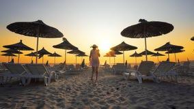 Kvinna i den vita klänningen på den tomma stranden på soluppgång Royaltyfria Foton