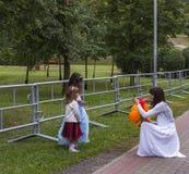 Kvinna i den vita klänningen som tar bilder av barn Arkivbilder