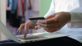 Kvinna i den vita skjortan som upp väljer ett kreditkortnummer på en bärbar dator stock video