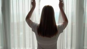 Kvinna i den vita t-skjortan som avtäcker gardiner och ser ut ur fönster Tycka om havssikten utanför lager videofilmer