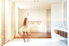 Kvinna i det vita badrummet med den dubbla vasken och att bada royaltyfria foton