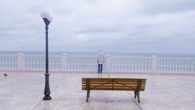 Kvinna i det vita omslaget och huven på härlig terrass med havssikt på strand tillbaka sikt arkivfilmer