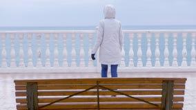 Kvinna i det vita omslaget och huven på härlig terrass med havssikt på strand tillbaka sikt stock video