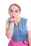 Kvinna i Dirndl med kyssen - truta - som isoleras på vit Arkivbilder