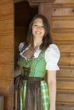 Kvinna i dirndlanseende i dörröppning med välkomnande gest Royaltyfria Bilder
