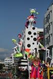 Kvinna i drottningdräkt som rider en flöte med karnevaldockor fotografering för bildbyråer