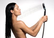 Kvinna i duschtvagningkropp under strömmen av vatten Arkivbild