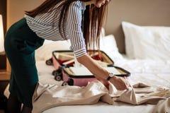 Kvinna i elegant kläder som packar saker in i lopppåsen som avgår från hotell arkivfoton