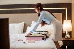 Kvinna i elegant kläder som packar saker in i lopppåsen som avgår från hotell arkivbild