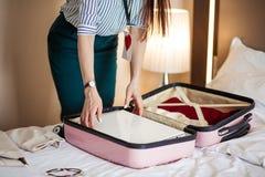 Kvinna i elegant kläder som packar saker in i lopppåsen som avgår från hotell royaltyfri foto