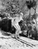 Kvinna i en baddräkt som skidar ner en kulle (alla visade personer inte är längre uppehälle, och inget gods finns Leverantörgaran Royaltyfri Fotografi