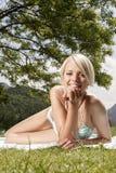Kvinna i en baddräkt som solbadar på gräs Arkivfoton