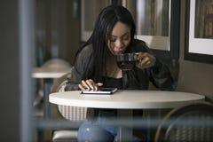Kvinna i en coffee shop med en minnestavla royaltyfri bild