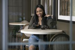Kvinna i en coffee shop med en smart telefon royaltyfri foto