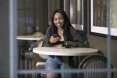 Kvinna i en coffee shop med en smart telefon royaltyfria bilder