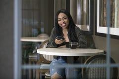 Kvinna i en coffee shop med en smart telefon arkivbild