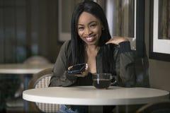 Kvinna i en coffee shop med en smart telefon arkivfoton