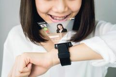 Kvinna i en digital klocka för vit klänningshow som visar digitala skärmar för att meddela ansikte mot ansikte royaltyfri fotografi