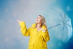 Kvinna i en gul regnrock på en grå bakgrund royaltyfria bilder