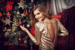 Kvinna i en guld- klänning bredvid en julgran royaltyfria foton