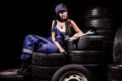 Kvinna i en gummihjulservice Arkivbild