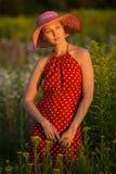 Kvinna i en hatt bland vildblommor på solnedgången Royaltyfri Foto