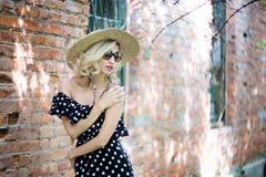 Kvinna i en hatt I lång prickklänning Retro italiensk stil Nära tegelstenväggen royaltyfri foto