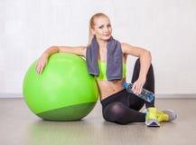 Kvinna i en idrottshall som vilar, når utbildning med konditionbollen Arkivfoton
