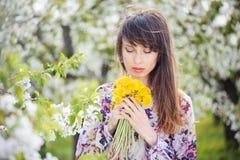 Kvinna i en körsbärsröd trädgård Arkivbilder