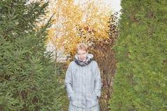 Kvinna i en lång grå regnrock arkivbild