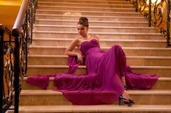 Kvinna i en lång klänning som ligger på trappan Fotografering för Bildbyråer
