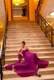 Kvinna i en lång klänning som ligger på trappan Royaltyfria Bilder