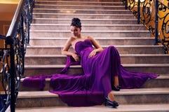 Kvinna i en lång klänning som ligger på trappan Royaltyfri Bild