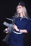 Kvinna i en marinlikformig med ett anfallgevär Royaltyfria Foton