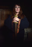 Kvinna i en mörk klänning med svärdet Royaltyfri Fotografi