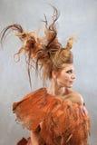Kvinna i en orange dräkt, stående, mode, studio royaltyfri foto