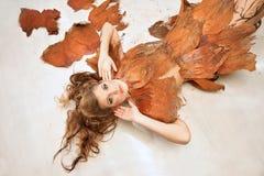 Kvinna i en orange utsmyckad dräkt som ner ligger, mode, studio royaltyfri foto