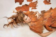 Kvinna i en orange utsmyckad dräkt som ner ligger, mode, studio royaltyfri bild