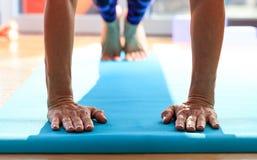 Kvinna i en pilatesgrupp som gör liggande armhävningar royaltyfri foto