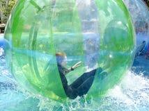 Kvinna i en plast- orb på vatten arkivbild