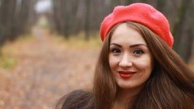 Kvinna i en röd basker och med röda kanter som smilling och ser in i den utomhus- kameran stock video