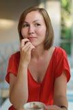 Kvinna i en röd klänning på kafét Fotografering för Bildbyråer