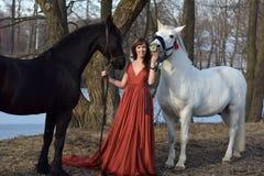 Kvinna i en röd lång klänning med två hästar royaltyfria foton