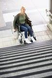 Kvinna i en rullstol framme av trappa Arkivfoton