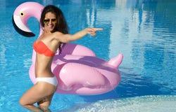 Kvinna i en simbassängfritid på en jätte- uppblåsbar jätte- rosa flamingoflötemadrass i röd bikini Royaltyfri Fotografi