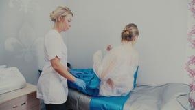 Kvinna i en special dräkt som förbereder sig för tryckterapitillvägagångssätt stock video